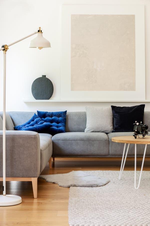 Echte foto van helder woonkamerbinnenland met eenvoudige affiche, metaallamp, grijs hoeklaag en tapijt royalty-vrije stock afbeeldingen