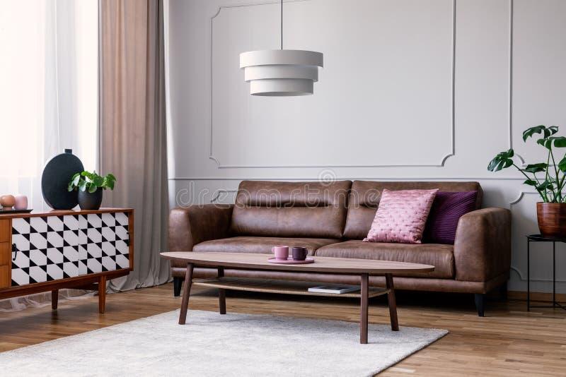 Echte foto van lichtgrijs woonkamerbinnenland met venster met gordijn, leerbank met hoofdkussens, koffietafel op tapijt en cupb stock foto's