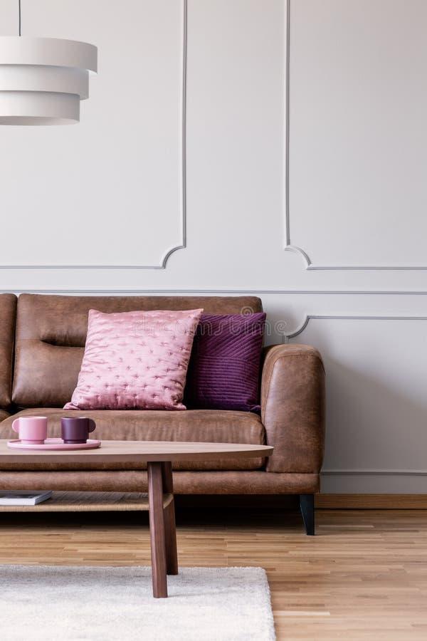 Echte foto van pastelkleur roze en violette die kussens op leerlaag worden geplaatst in lichtgrijs woonkamerbinnenland met houten royalty-vrije stock foto