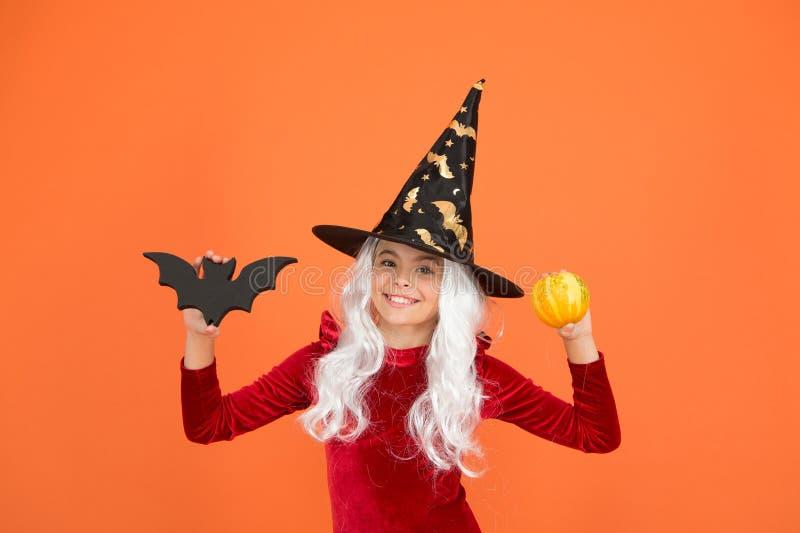 Echte heks in vermomming Happy little witch orange background Klein heks meisje houdt vleermuis en pompoen Halloween-kind royalty-vrije stock foto