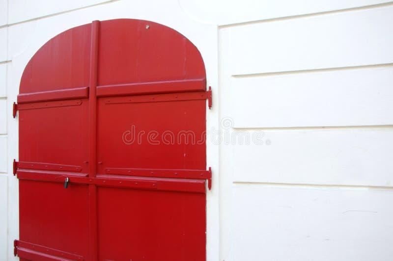 Echte heldere rode buitendeurblinden en witte muur stock afbeelding