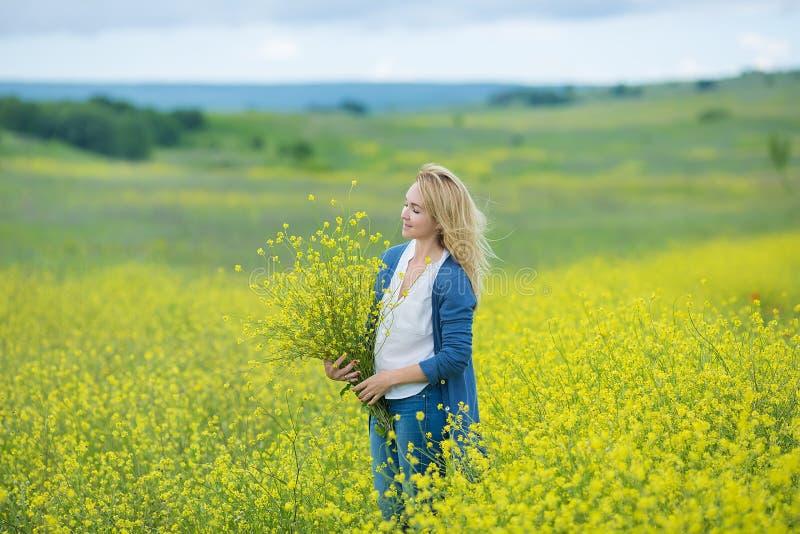Echte leuke damevrouw die in weide van gele bloemen bloemboeket snuiven Aantrekkelijk mooi jong meisje die van de warme som genie royalty-vrije stock foto