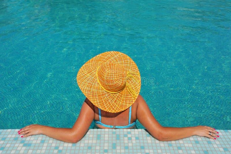 Echte vrouwelijke schoonheid ontspannen in zwembad stock fotografie
