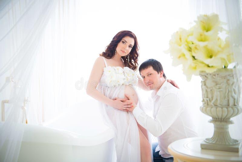 Echtgenoot die de buik van een zwangere vrouw met tederheid en zorg koesteren royalty-vrije stock fotografie