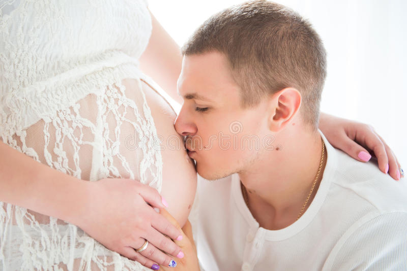 Echtgenoot die en zwangere buik van zijn vrouw koesteren kussen, close-upportret royalty-vrije stock foto