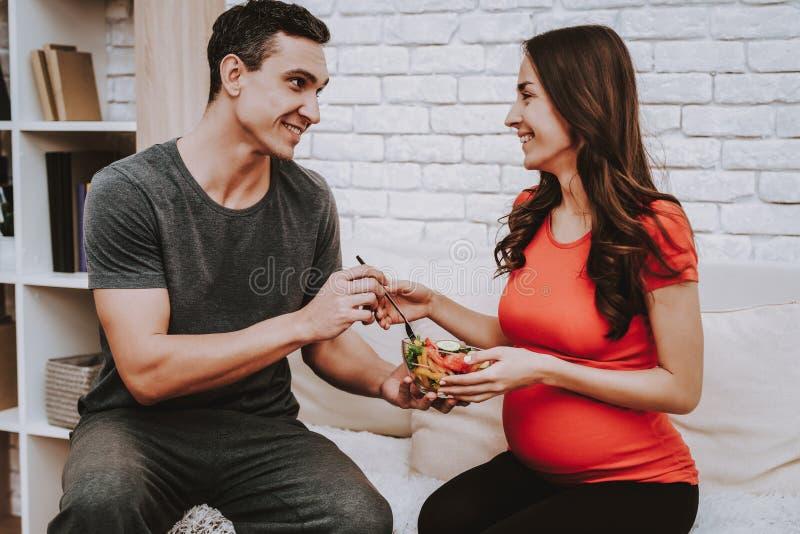 Echtgenoot en zwangere vrouw Het eten van salade Voedsel stock foto's