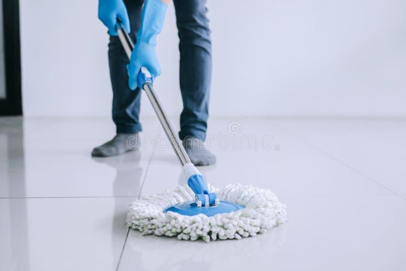 Echtgenoot huishouden en het schoonmaken concept, Gelukkige jonge mens in bl stock fotografie