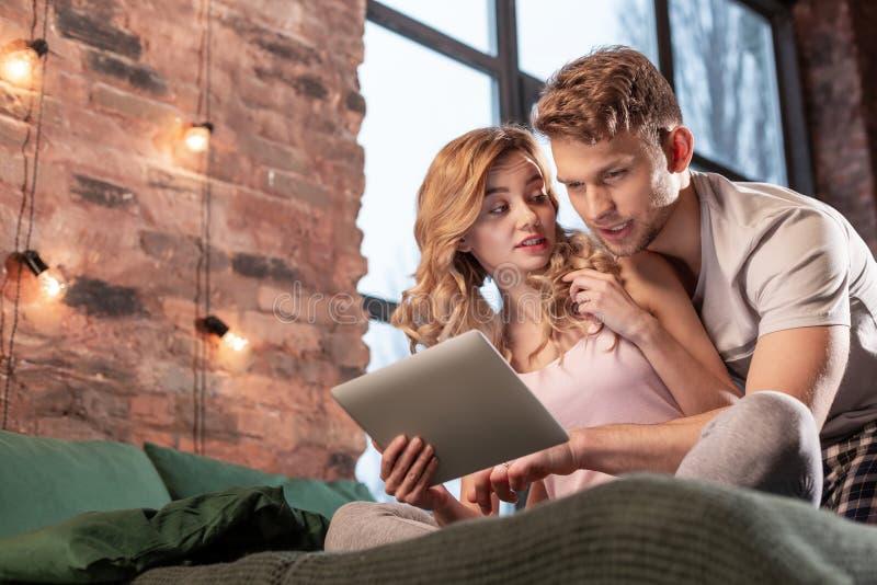 Echtpaar die enkel de plaats zoeken naar diner in Internet die tablet gebruiken stock fotografie