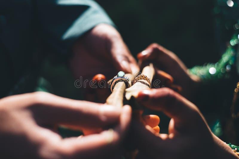 Echtpaar met traditionele huwelijkskleding die hun trouwringen in een donkere verlichting tonen stock afbeelding