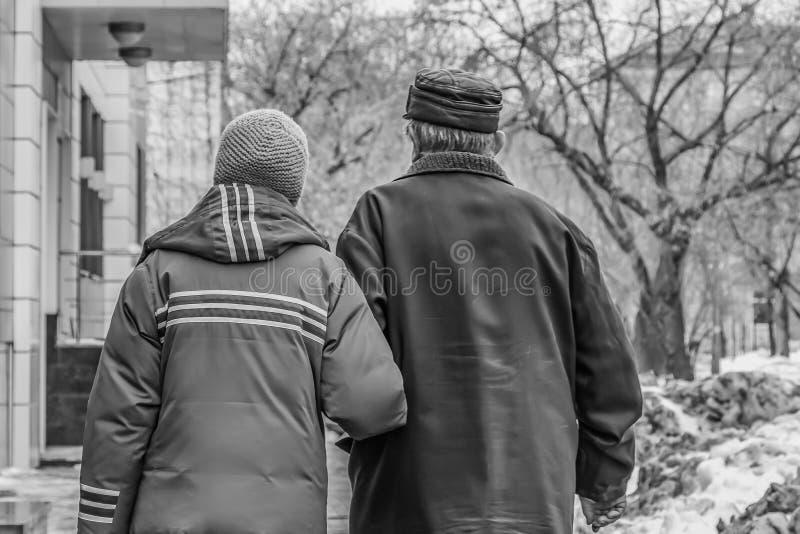Echtpaar van gepensioneerden die wapen-in-wapen in de straat met huizen en bomen en vuile sneeuw in de winter en een bejaarde lop stock foto