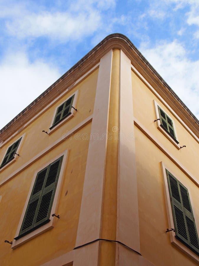 Eckansicht von typischen menorcan spanischen Bautenanstrichfarbe das Gelb, das aufwärts mit einem blauen Sommerhimmel und weißen  lizenzfreie stockbilder