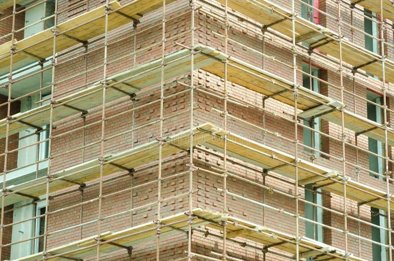 Ecke des Hochbaustandorts des roten Backsteins mit Baugerüst stockfoto