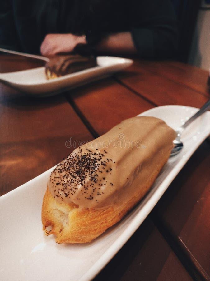 Eclair капучино на печенье в плите стоковые фотографии rf