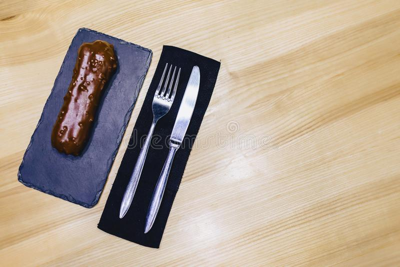 eclair de chocolat délicieux avec une fourchette et un couteau photographie stock