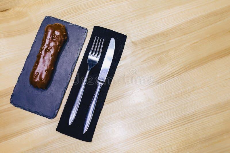 eclair de chocolate delicioso com uma forquilha e uma faca fotografia de stock