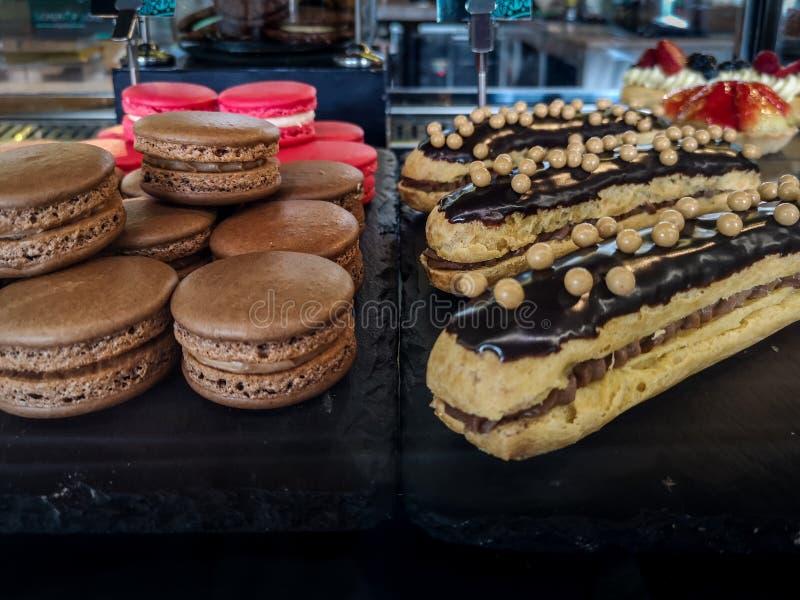 Eclair de chocolate et macarons frais - desserts délicieux photographie stock libre de droits