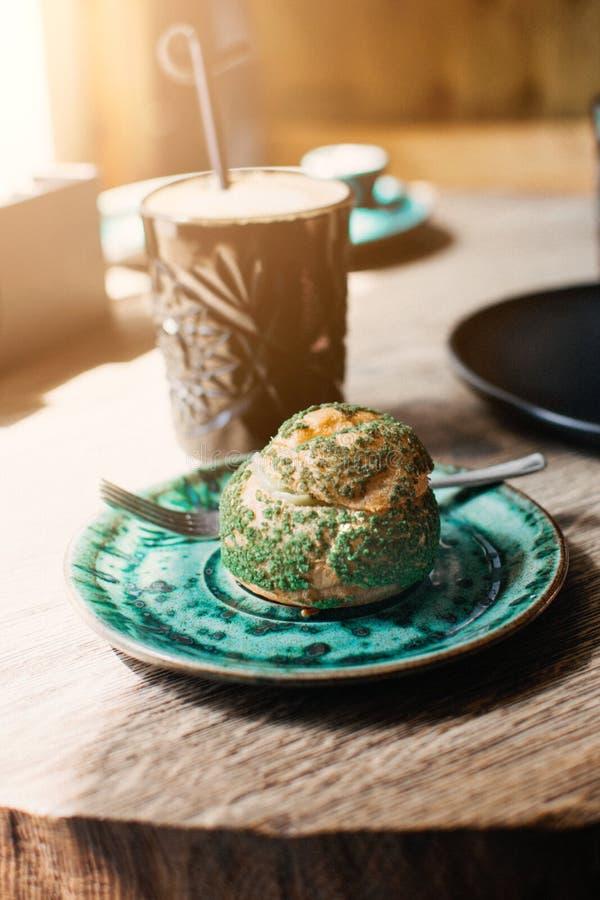 Eclair de pistache, profiterole dans le lustre du plat vert sur la table, fin  Eclair, tarte de crème anglaise avec de la crème d photo libre de droits