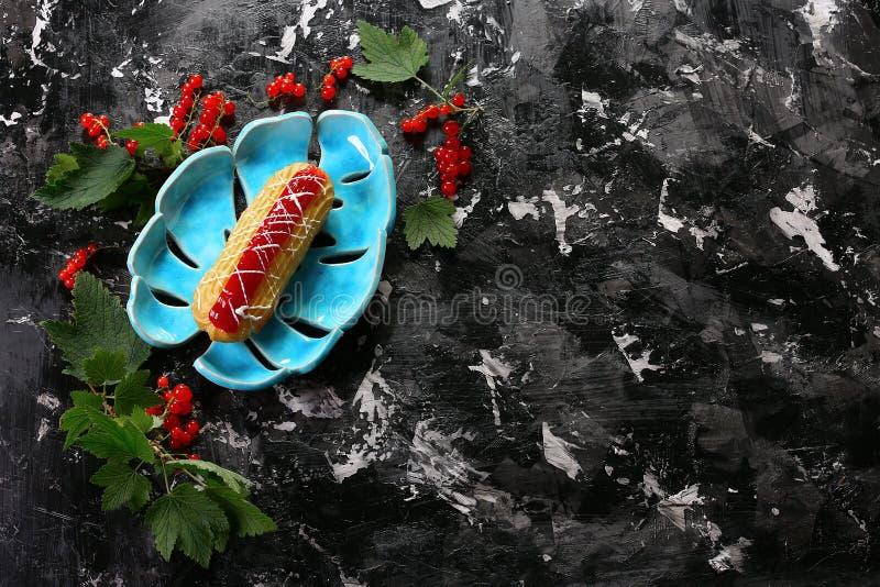 Eclair doce com doce com os corintos vermelhos das bagas em uma placa decorativa azul, no fundo escuro Sobremesa do fruto do verã fotografia de stock royalty free