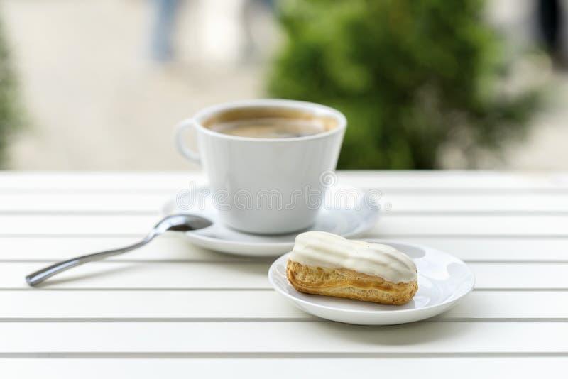 Eclair fresco con el chocolate y la taza blancos del café express, café sólo en la tabla de madera blanca Almuerzo de domingo el  fotos de archivo