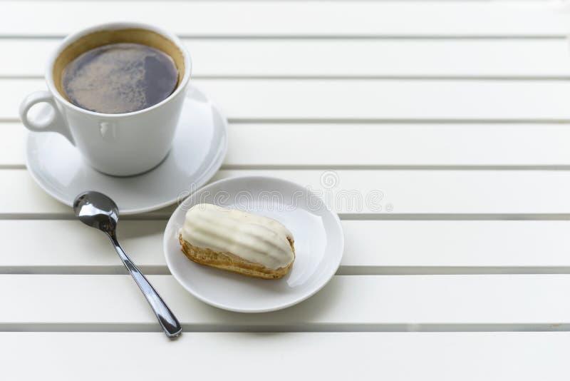 Eclair fresco con el chocolate y la taza blancos del café express, café sólo en la tabla de madera blanca, fondo con el espacio d fotografía de archivo