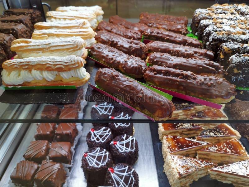 Eclair med piskad kräm och choklad - kakor royaltyfri foto