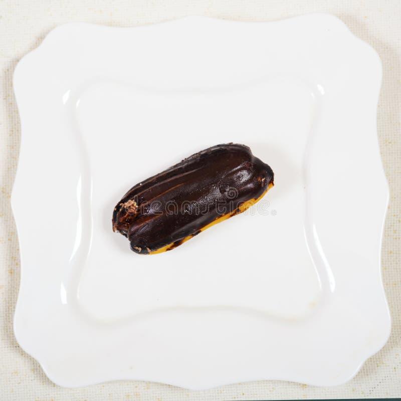 Eclair tort na bielu talerza tle, fotografia royalty free