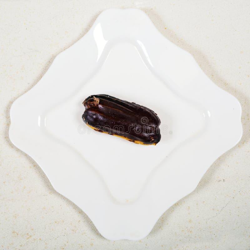 Eclair tort na bielu talerza tle, obrazy stock