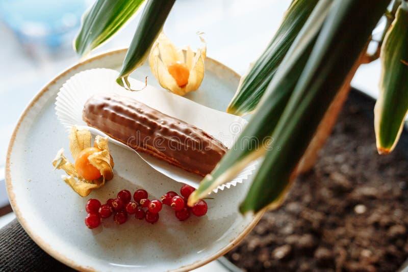 Eclairkuchen auf einer Platte verziert mit Zitrusfrucht und Beeren und Blätter eines Houseplant im Vordergrund stockfoto