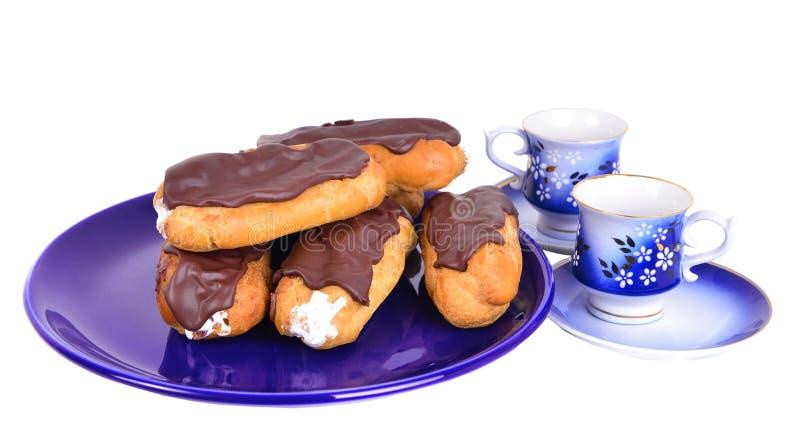 Eclairs στο μπλε πιάτο με τα φλυτζάνια coffe στοκ εικόνα