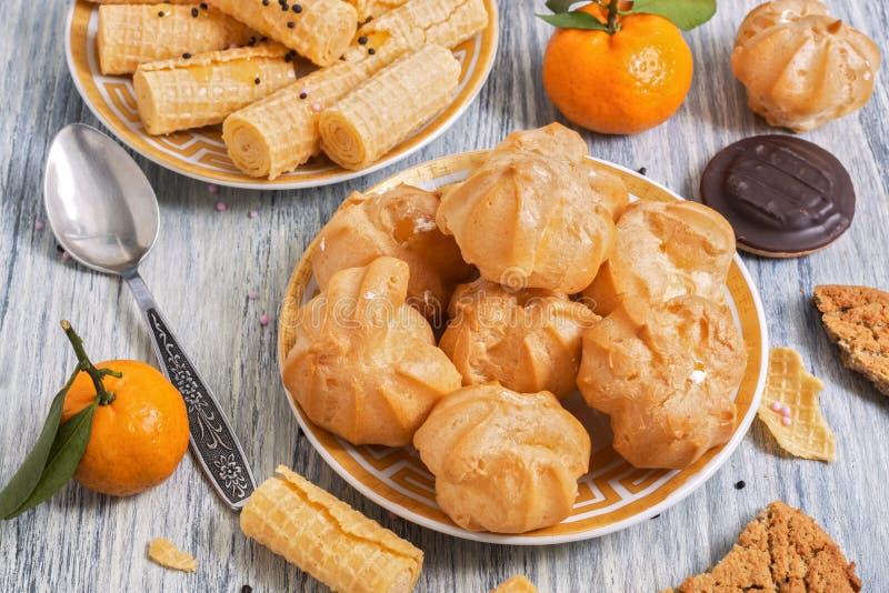 Eclairs торта с сливк на деревянном столе На заднем плане кудрявые вафли и tangerines Селективный фокус стоковые фотографии rf