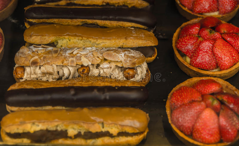 Eclairs with almonds and chocolate and dessert with strawberries. Sweet cake stock images