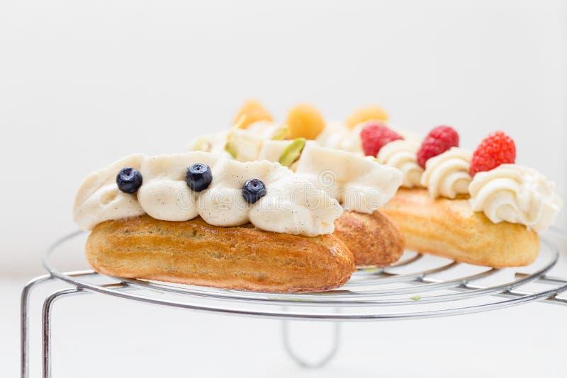 Eclairs avec de la crème de vanille sur le fond blanc photo libre de droits