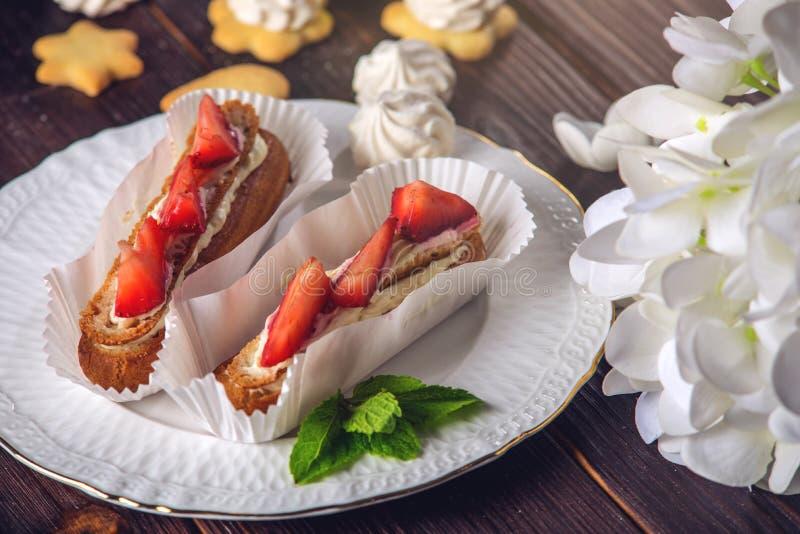 Eclairs caseiros deliciosos dos bolos com morangos e creme em um patamar de madeira e em uma parte na placa fotos de stock royalty free