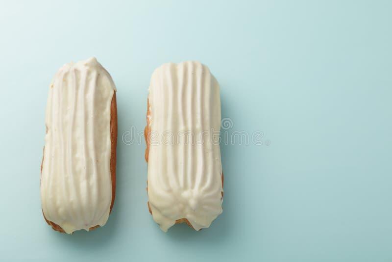 Eclairs com o esmalte branco do chocolate no fundo azul do ovo do pato fotos de stock royalty free