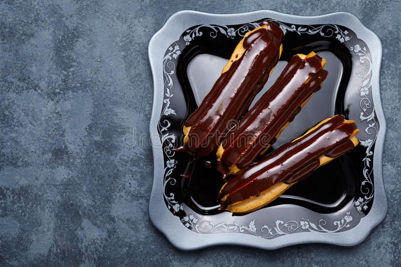 Eclairs con el chocolate y la crema azotada en fondo negro del plato imagen de archivo