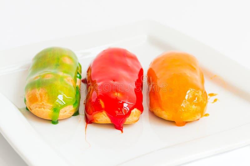 Eclairs con el esmalte colorido del caramelo imagen de archivo