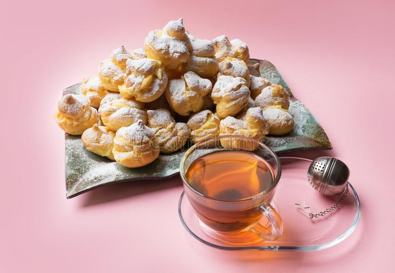 Eclairs délicieux arrosés avec du sucre glace et la tasse de thé sur un fond rose Profiteroles faits maison photo stock