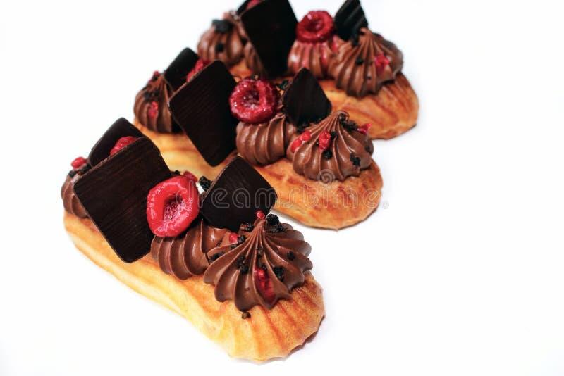 Eclairs del chocolate y de la frambuesa con las decoraciones del chocolate y las bayas frescas imagenes de archivo