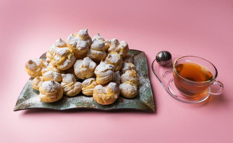 Eclairs deliciosos asperjados con el azúcar de formación de hielo y la taza de té en un fondo rosado Profiteroles hechos en casa fotos de archivo