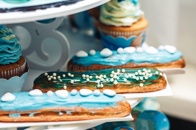 Eclairs deliciosos con crema de la turquesa y el primer de las magdalenas en la tabla festiva imagenes de archivo