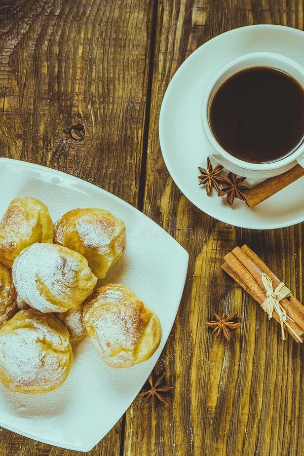 Eclairs deliciosos polvilhados com o açúcar de crosta de gelo, suporte em uma tabela de madeira Copie o spase foto de stock