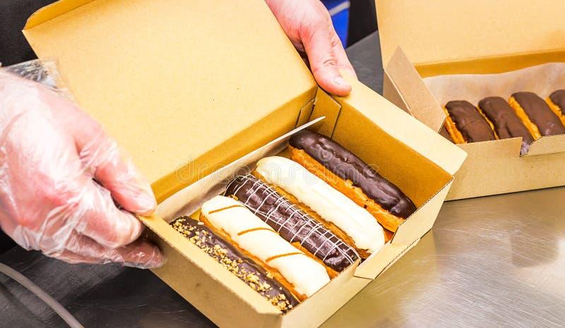 Eclairs do creme com chocolate da obscuridade e da luz em uma caixa imagem de stock
