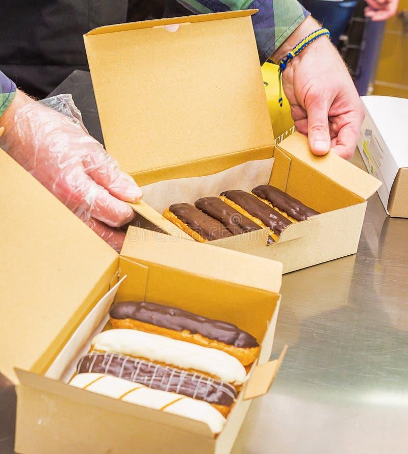 Eclairs do creme com chocolate da obscuridade e da luz em uma caixa imagem de stock royalty free