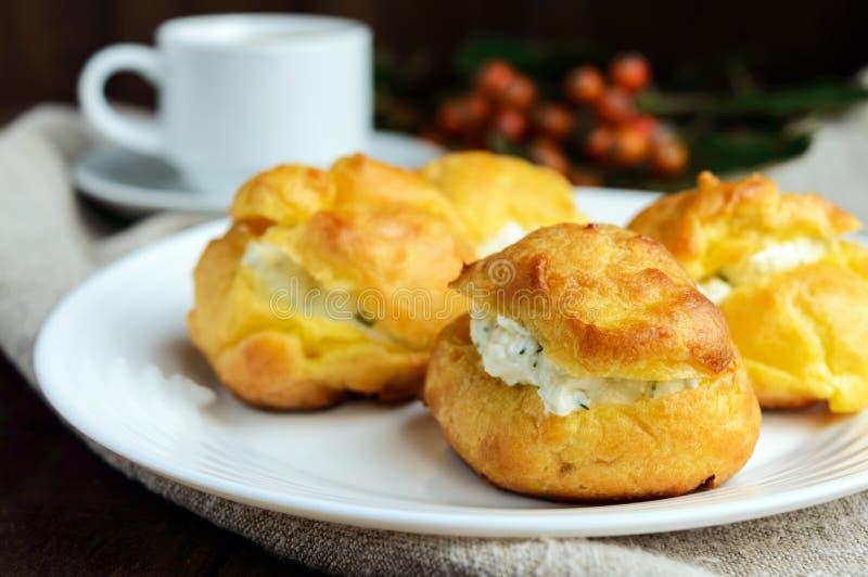 Eclairs fraîchement cuits au four de petits pains bourrés du fromage blanc épicé et d'une tasse de café et de x28 ; espresso& x29 photos stock
