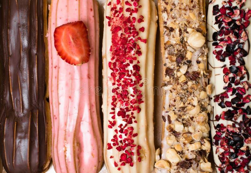 Eclairs franceses doces e coloridos com berrys, chocolate, porcas Grupo de sobremesa francesa Fundo do Eclair Ecl colorido delici fotos de stock royalty free