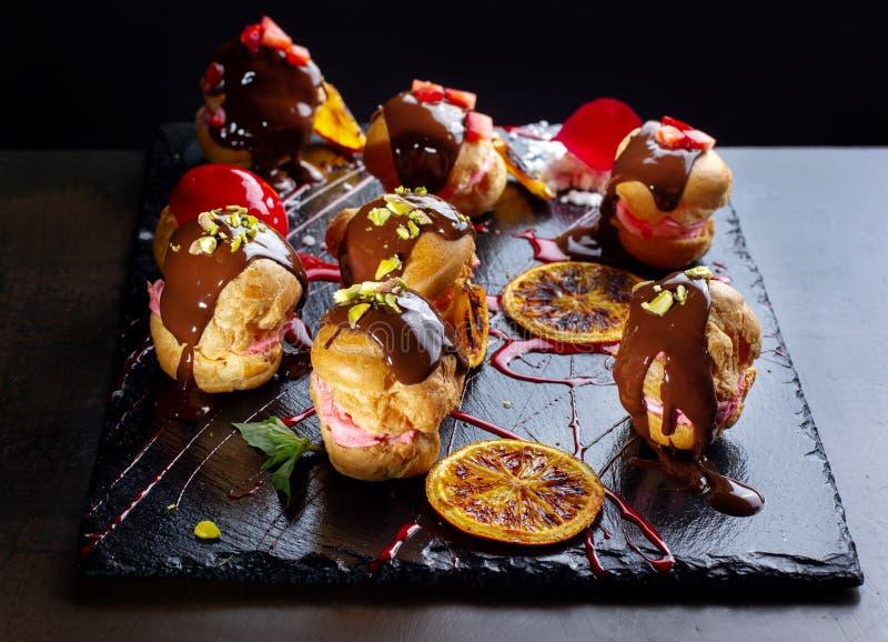 Eclairs franceses tradicionales con el chocolate y las nueces fotos de archivo