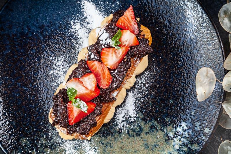 Eclairs francesi tradizionali serviti sul piatto scuro premio Alimento per la prima colazione con lo spazio della copia Classico  immagini stock libere da diritti