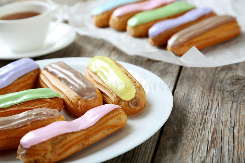 Eclairs with glaze. On a grey wooden table stock photo