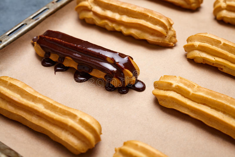Eclairs med choklad och piskad kräm som förbereder sig på bakplåten arkivfoton