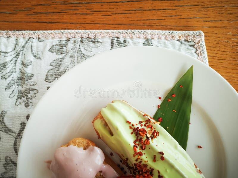 Eclairs med kulör glasyr på en vit platta Hemlagade eclairskakor Traditionella eclairs, yrkesmässiga klassiker, eclairsfransman royaltyfria bilder